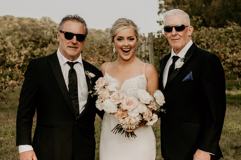 bride and two fathers at altar in generation tux suits