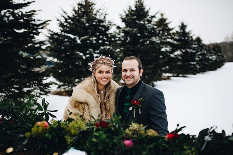 Groom in Iron Gray Suit with bride with trees in snow