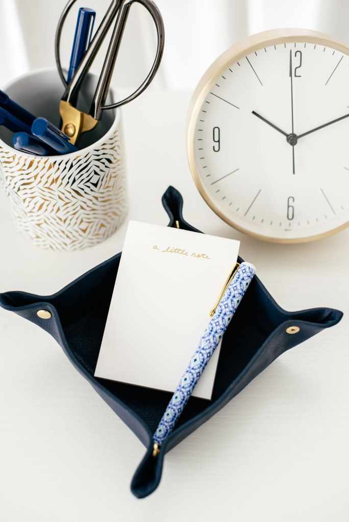 notebook and pen with a clock and cup of desk supplies