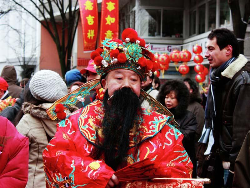 Қытайдағы Санта Клаус: Шан Трасс Лаиден қызыл халат пен күрделі бас киім киеді