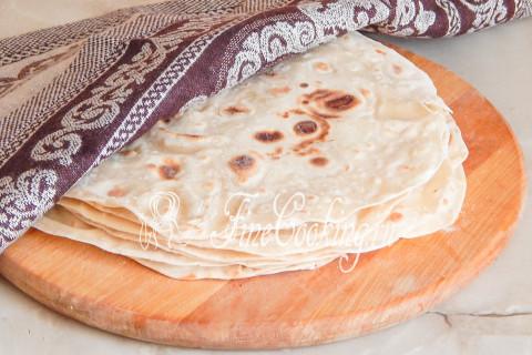 De afgewerkte dunne pita wordt uit de koekenpan verwijderd en onmiddellijk, terwijl het heet is, sprenkel het uit de verpulvervorming met water