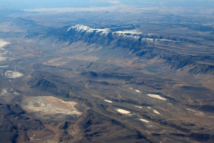 Steens Mountain, a tilted fault-block in southern Oregon. The Basin and Range Province extends northward into Oregon, as can be seen here in this view south towards Steens Mountain. The frontal fault of the range runs along its eastern base, and in classic tilted fault-block style, the range tilts back away from the fault, towards the west. Steens Mountain consists mostly of Miocene basalt. (ID: 30-3381)