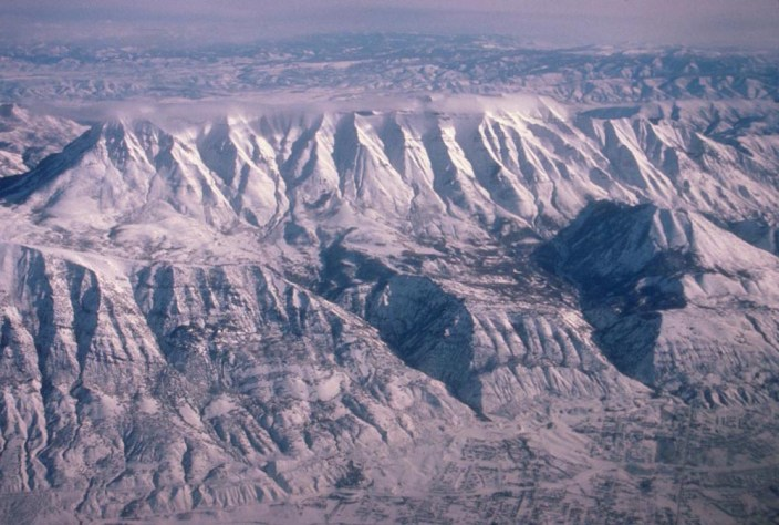 The eastern edge: Mt. Timpanogos, in the Wasatch Range of Utah. Mt. Timpanogos is the second highest peak of the Wasatch Range, at an elevation of 11749'. The Wasatch Range rises along the Wasatch fault, which is an active fault, and so poses a significant earthquake hazard to the Salt Lake City region. As evidence of recent faulting, two wineglass canyons can be seen behind the fault on the right side of the photo. (ID: 477-89)