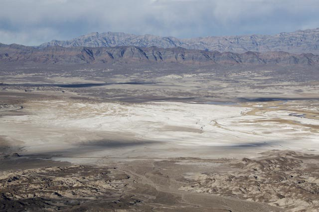 View of Tecopa Basin, the south end of the Amargosa Valley. From the top of Tecopa Peak, one gets a wonderful view of the south end of the Amargosa Valley. In the middleground lies Lake Tecopa, surrounded by Plio-Pliestocene lake bed deposits. The mountains in the background are the Resting Spring Range (closest) and the Nopah Range. Both consist of predominantly Cambrian rock that has been tilted and faulted during crustal extension.