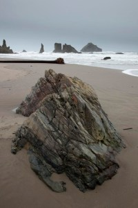 High tide pulling sea stacks toward a blueschist block on Bandon Beach, Oregon