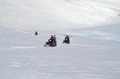 The team trade;ling on snow mobiles to the wind scoop by Vesleskarvet