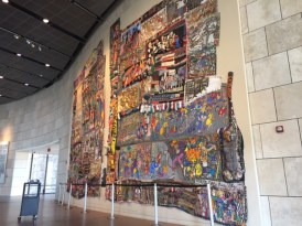 An enormous mural made of textiles by Aminah Brenda Lynn Robinson fills a wall at the National Underground Railroad Freedom Center