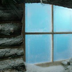 A window of a snowed in wooden cabin