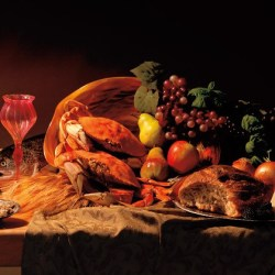 A feast consisting of pink wine, fruits, crabs and bread on a wooden table