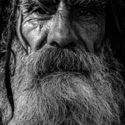 Black and white closeup of an old bearded man