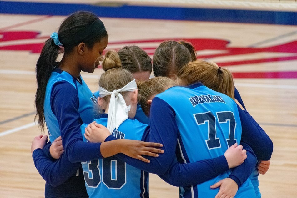 Georgia Adrenaline Volleyball players pray before a game