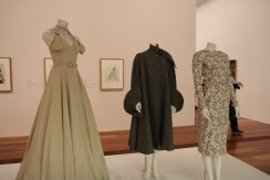 The evening dress alongside two other garments Hall Ludlow designed for Peggy Stone, on display at the National Gallery of Victoria