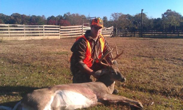 young man poses with a great deer