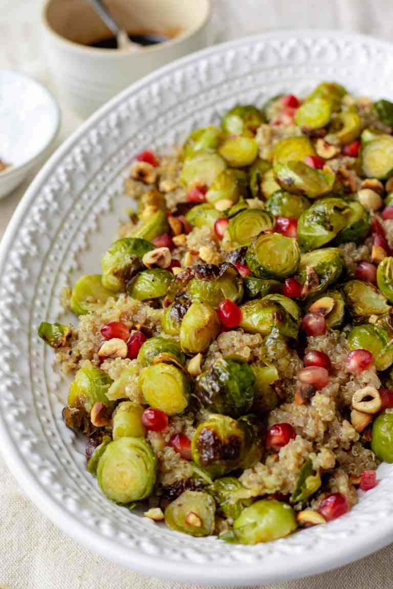 This is the festive salad of your dreams! Maple roasted brussel sprouts tossed with nutty quinoa, fresh apple, crunchy toasted hazelnuts and tangy pomegranate all liberally drizzled with a sticky balsamic reduction. The most perfect pretty lunch. Vegan, GF & healthy!