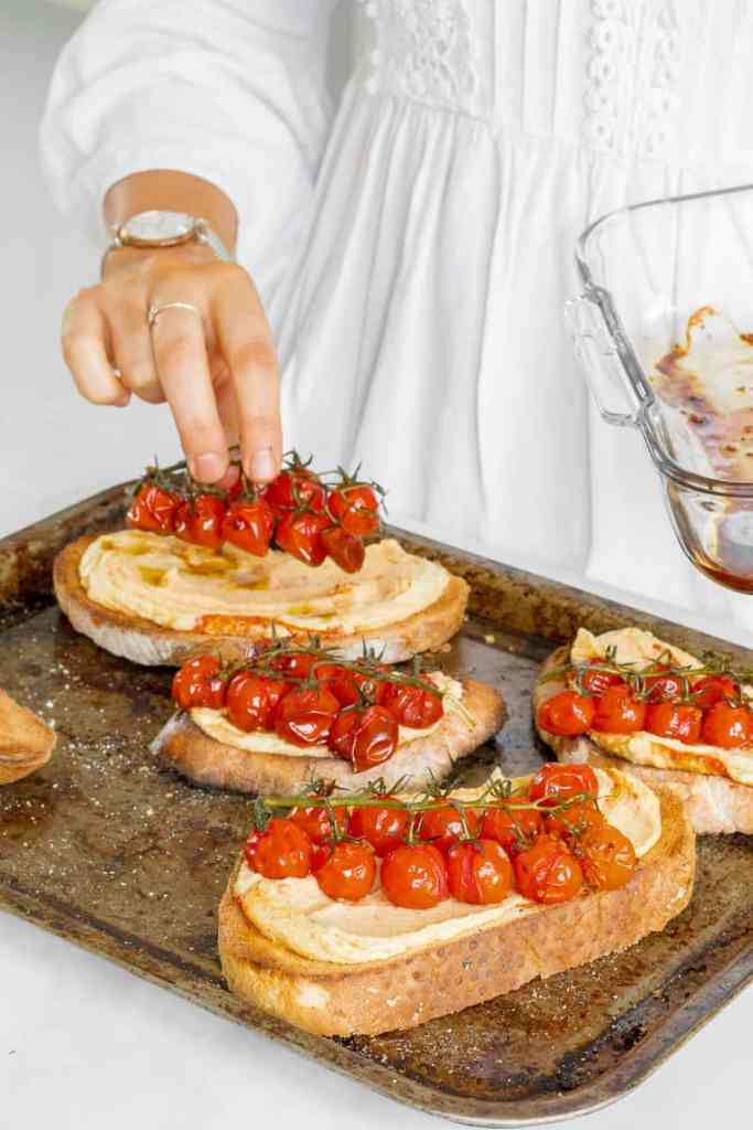 Layering the balsamic tomatoes on top of the sourdough toast.