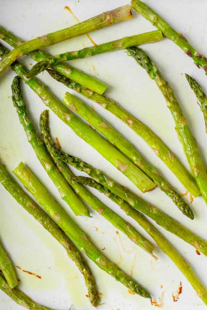 Roasted asparagus in a white baking dish.