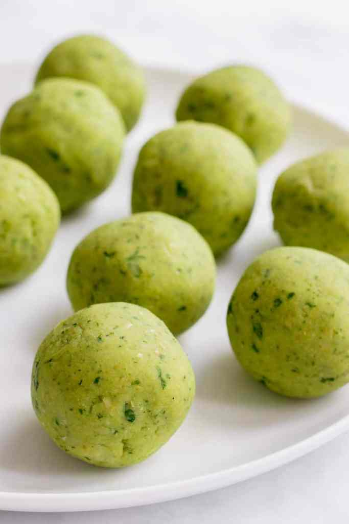 Balls of uncooked falafel on a plate.