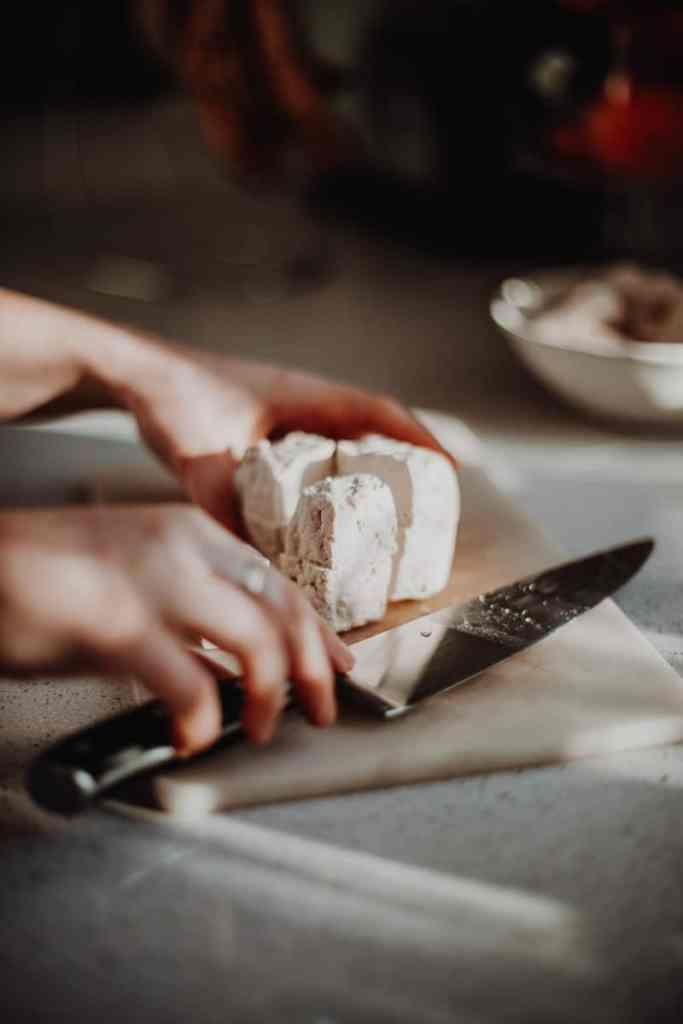 Chopping tofu into chunks.