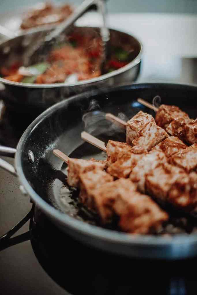 Satay tofu skewers frying in a pan.