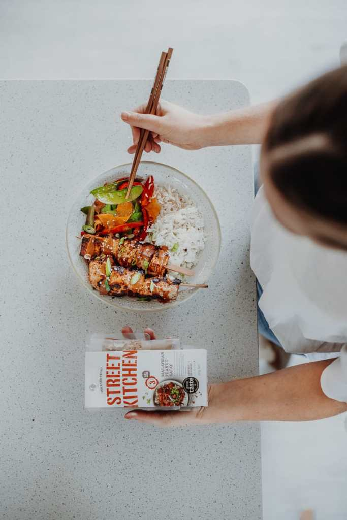 Overhead shot of rainbow Stir-fry with satay tofu skewers and Street Kitchen package.