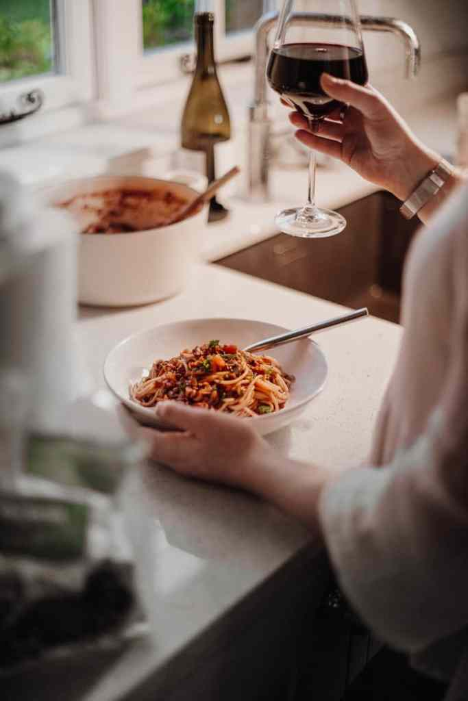 Enjoying the Best Ever Lentil Bolognese with a glass of red wine - Vegan, GF & Healthy! Georgie Eats.