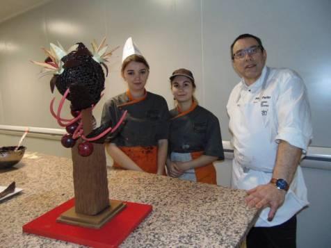 Marie-Amélie et Océane en compagnie de leur enseignant M. Paris devant une pièce en chocolat réalisée pour l'occasion.