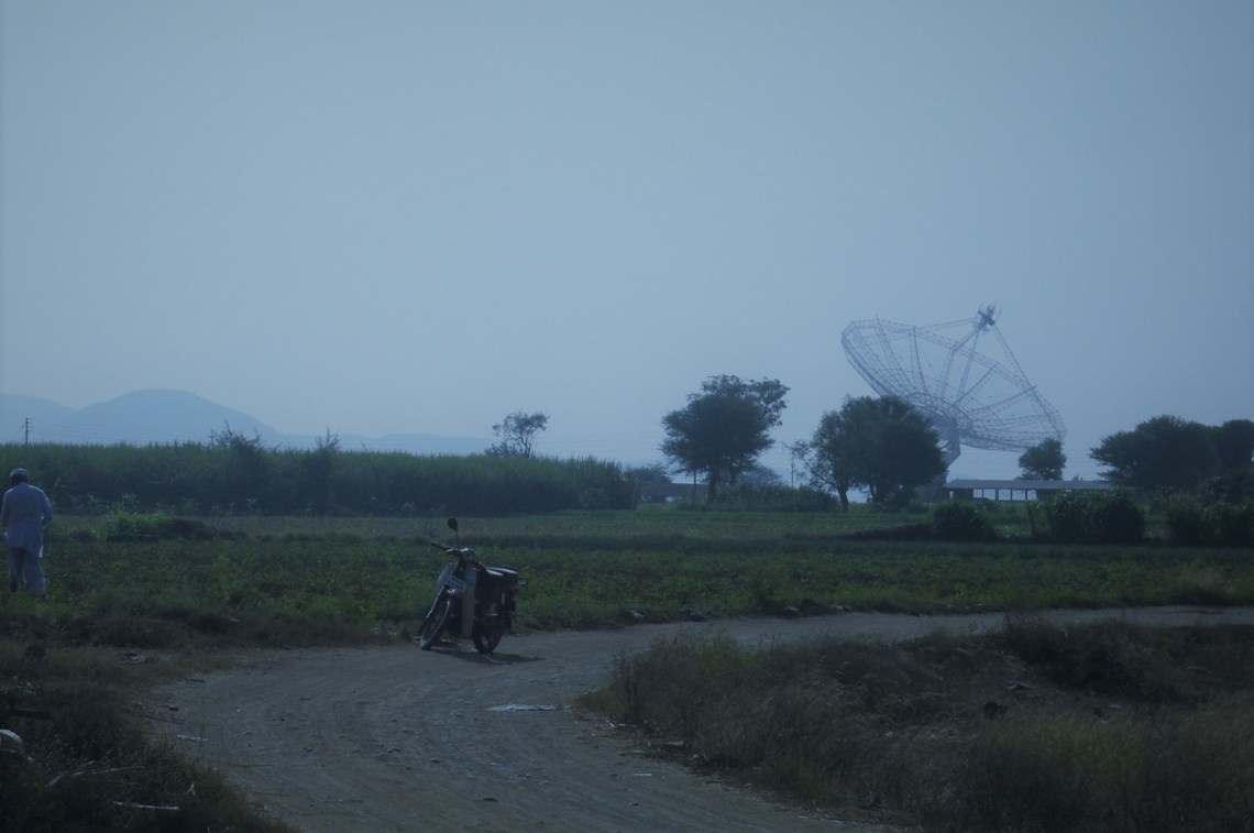 A dirt road with a radio telescope in the distance