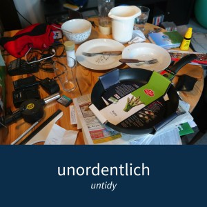 "Image showing an untidy table and the caption ""unordentlich - untidy"""
