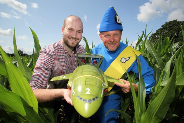 York Maize Maze 2015...Seen here the York Maize Maze which this year celebrates the 50th anniversary of Thunderbirds (1965-2015) with a giant Thunderbird 2 carved out of an 18 acre field of maize plants to create a giant maze.  Seen here; farmer and maze creator TOM PEARCY dressed as the Thunderbird character 'Virgil Tracy', alongside JAMIE ANDERSON, director of Anderson Entertainment and son of the late Gerry Anderson; creator of Thunderbirds with a model of Thunderbird 2. York Maize Maze is the largest maze in the UK, and the largest Maize Maze in Europe, and one of the largest in the world. The 300m metre long Thunderbird 2 is the largest representation of a Thunderbird anywhere in the world.