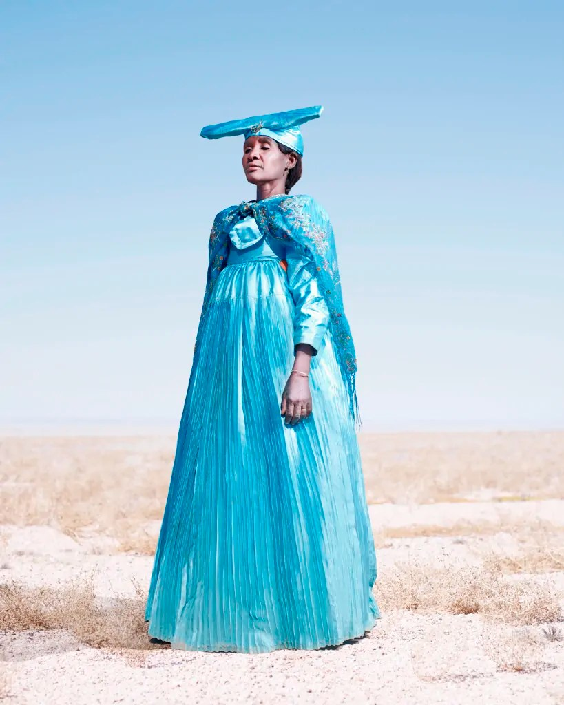 "Jim Naughten: Herero Woman in Blue (2012) @ Mariane Ibrahim Gallery Der britische Fotograf Jim Naughten lebt und arbeitet in London. 2012 hat er in Namibia Portraits von Hererofrauen und –männern fotografiert sowie Prozessionen bei der jährlichen Gedenkveranstaltung an den Kolonialkrieg. Zu den Portrait schreibt er: ""By composing these portraits against the Namibian landscape — one of unforgiving intensity but also of silent witness — there is an enlivening that takes place in an otherwise frozen moment. The still space, the direct gaze, the re-appropriated cloth combine to curate a stillness that allows the past to speak."""