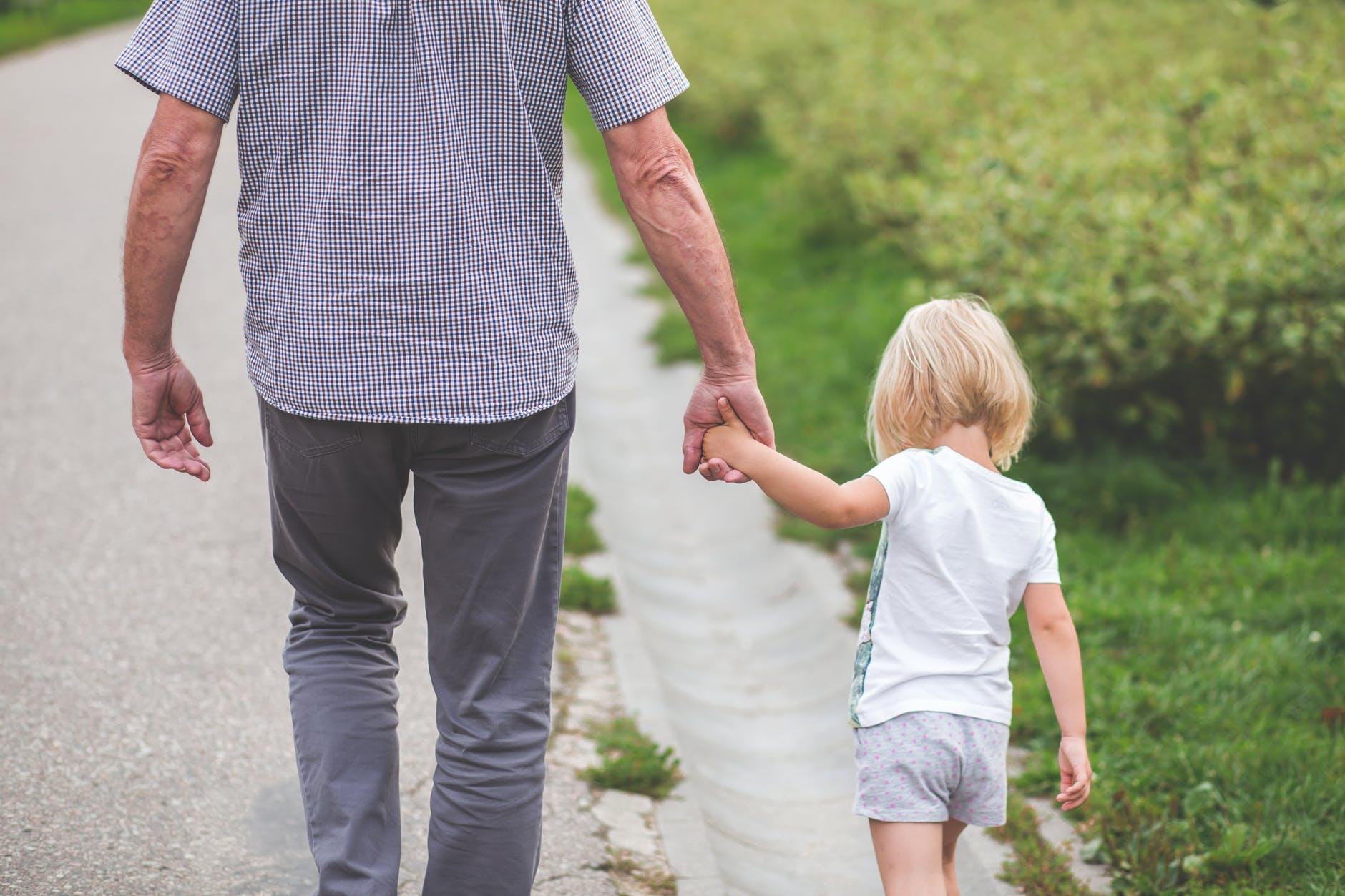 man and child walking near bushes during daytime