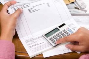 Imagen de una persona leyendo una factura y haciendo cálculos con una calculadora.