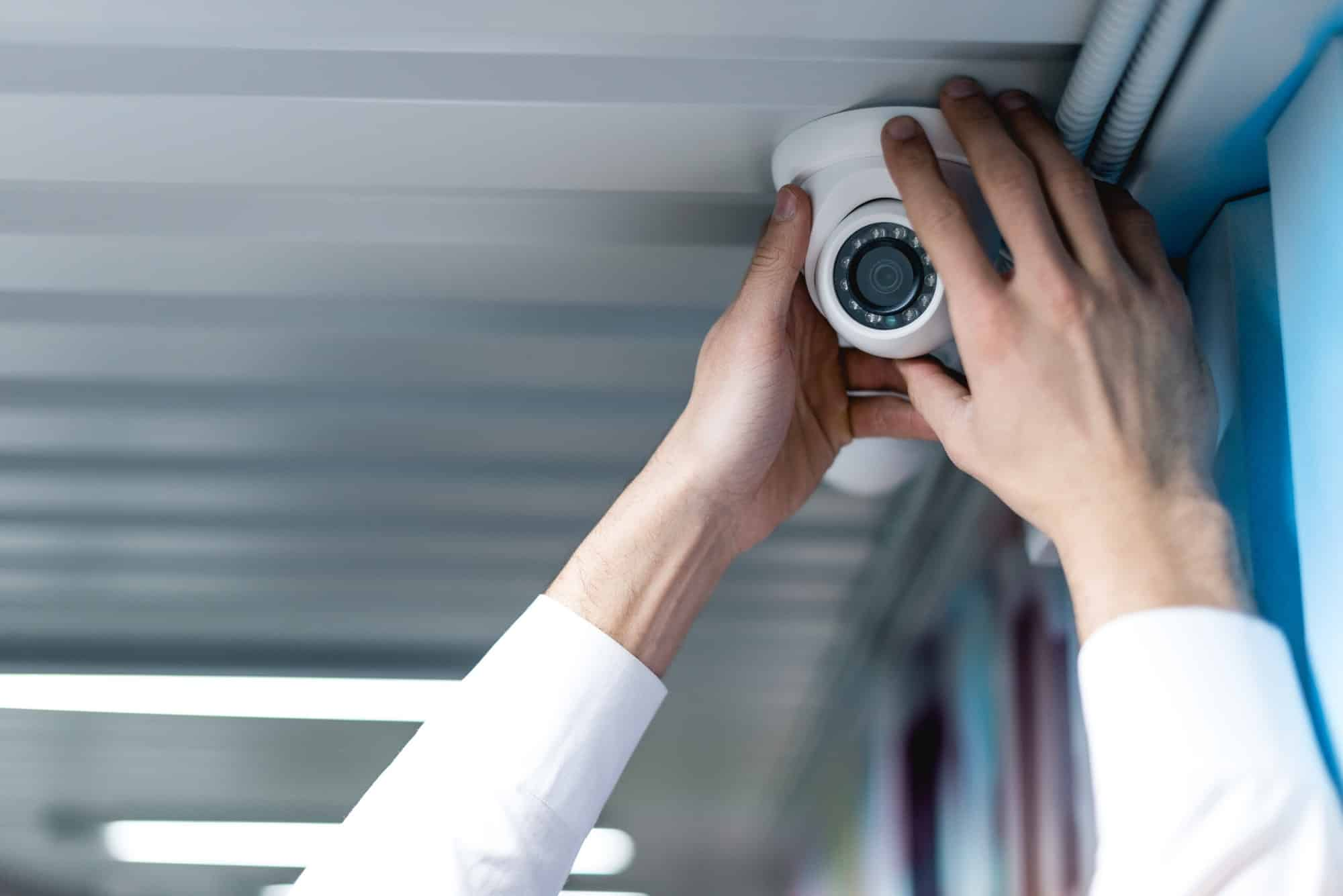 partial view of man setting up security camera