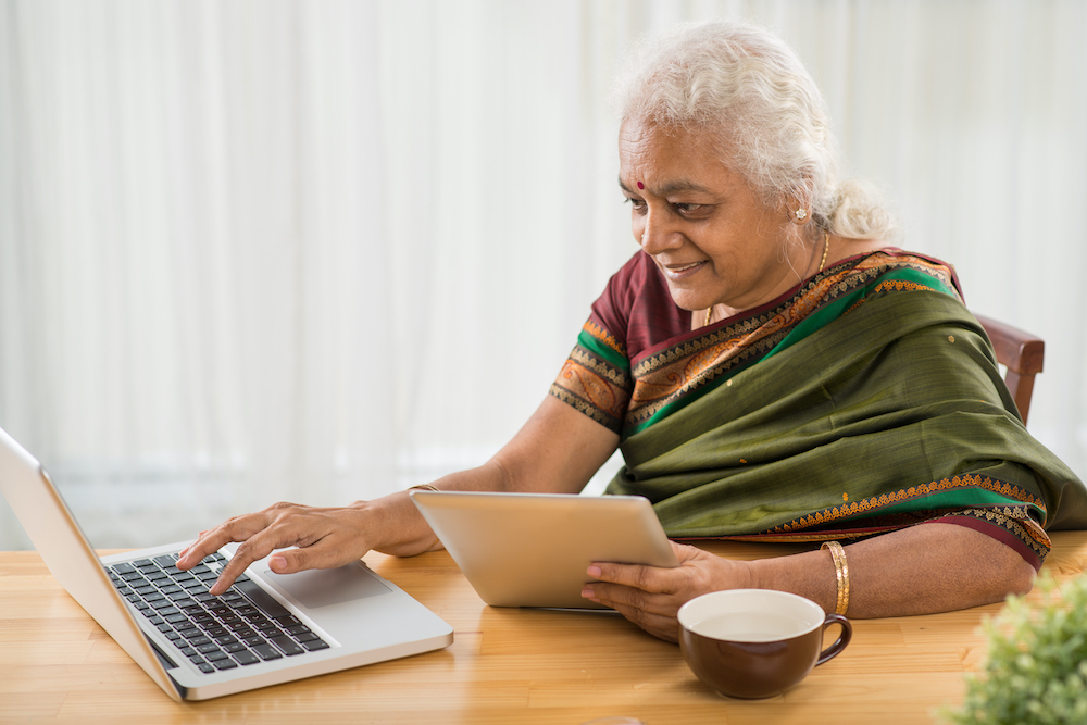 Senior Indian woman learning how to use digital tablet and laptop