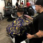Barber, Luis, designing a Warriors Logo on the back of client head