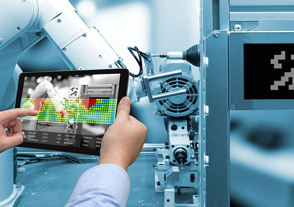 person holding tablet with robotic arm in front freepoint technologies
