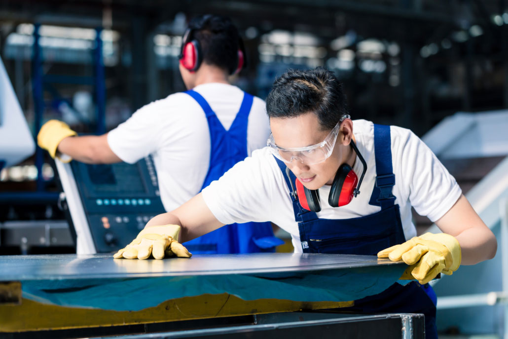 workers in factory working with metal sheets wearing safety glass and ear protection freepoint technologies
