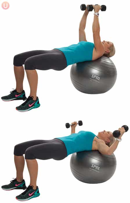 Chris Freytag demonstrating Stability Ball Chest Fly in a blue tank top on a silver stability ball