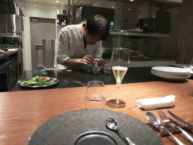 Chef wroring in the open kitchen seen from the counter at Michelin starred restaurant Hiroto in Hiroshima, Japan
