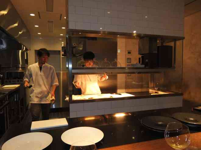 Chefs at work in open kitchen seen from the counter at Michelin starred restaurant Hiroto in Hiroshima, Japan