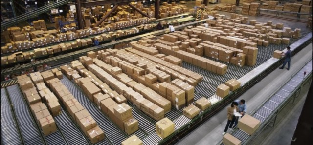 Image shows a large warehouse with a lot of boxes and people on the warehouse floor