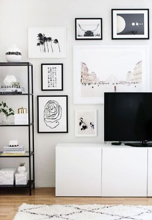 A TV console in the center of a wall gallery.