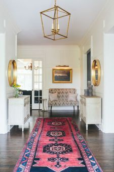 Entryway with patterned red and pink rug and golden frames.