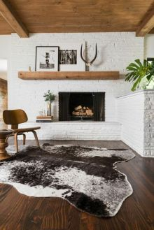 A minimal mantel is flawlessly matched with a wooden ceiling and white brick.