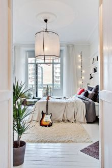 A beautiful bohemian bedroom with a central hanging light.