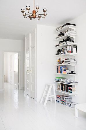 A series of floating shelves with numerous novels.