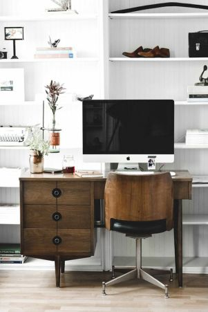 A dark wood modern desk and chair set with clean white shelves.