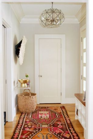 A boho entryway features honey oak hardwood floors layered with a colorful killim rug.