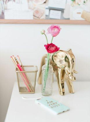 A golden elephant arranged next to a wire pencil basket.