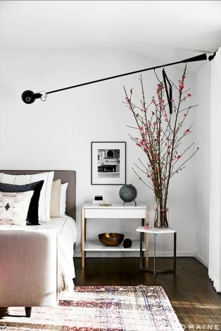 Neutral bedroom with branches, modern lighting, and a white side table.